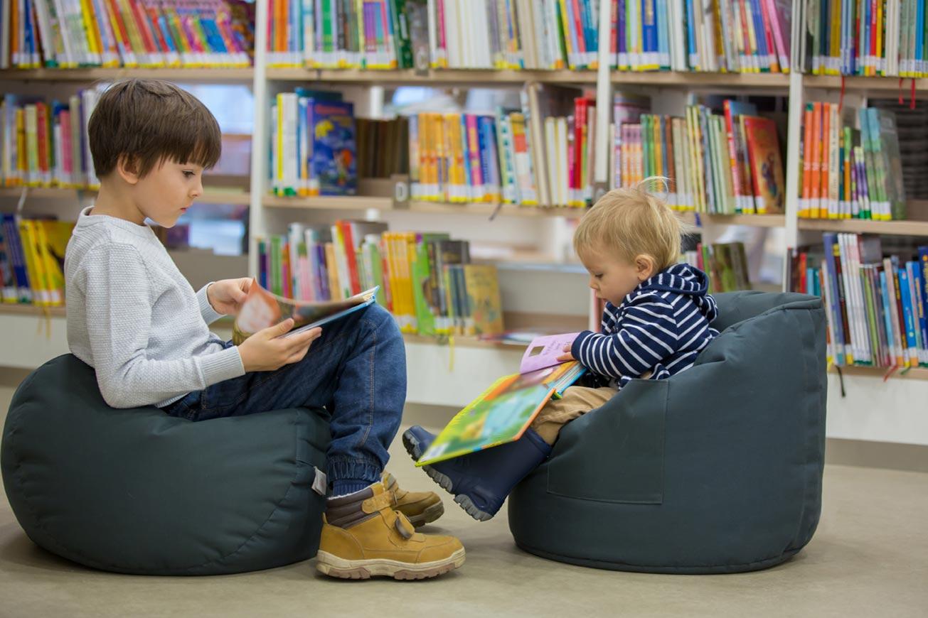 corso tradurre testi per ragazzi, due bambini leggono seduti nel un reparto editoria per ragazzi di una libreria
