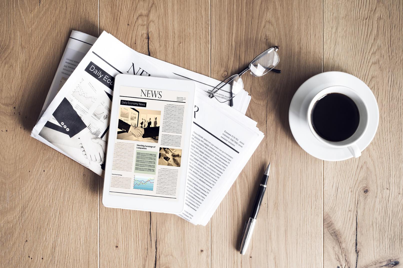 Ufficio stampa, giornali su un tavolo, occhiali tazza caffè penna