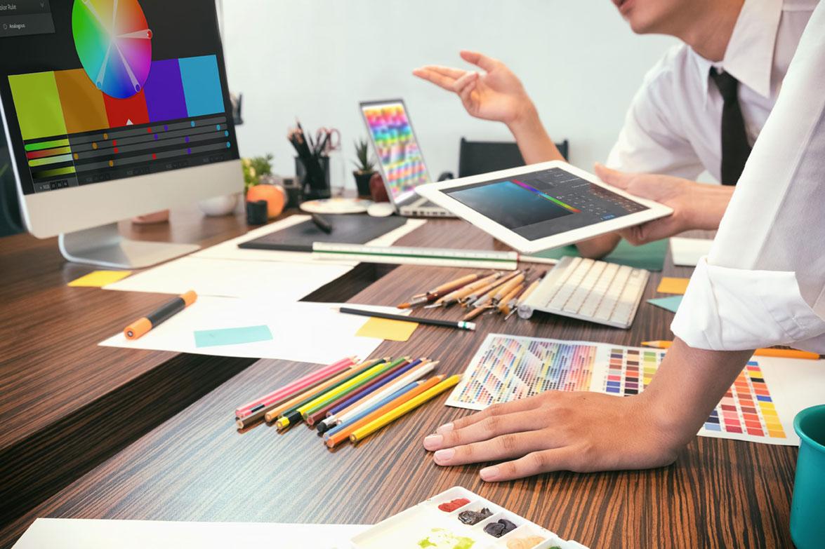 Impaginazione, grafici al lavoro davanti al pc, colori e palette