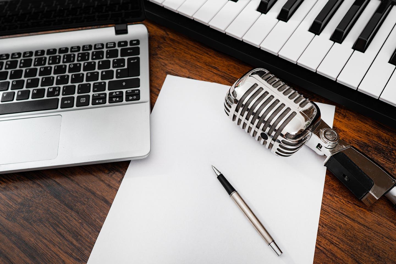 Corso tradurre testi musicali, tastiera microfono pc foglio e penna
