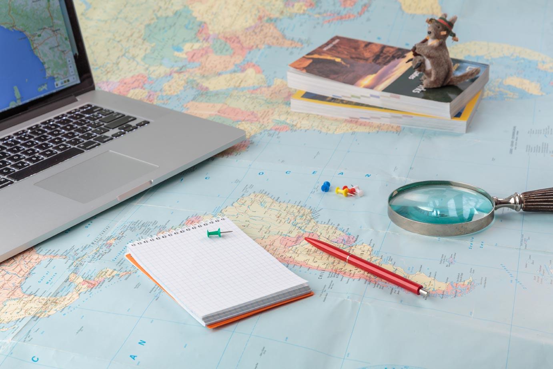 corso tradurre testi turistici, planisfero, pc penna e taccuino con una lente di ingrandimento